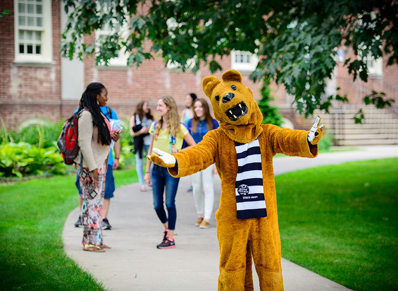 Lion mascot with students in the background.