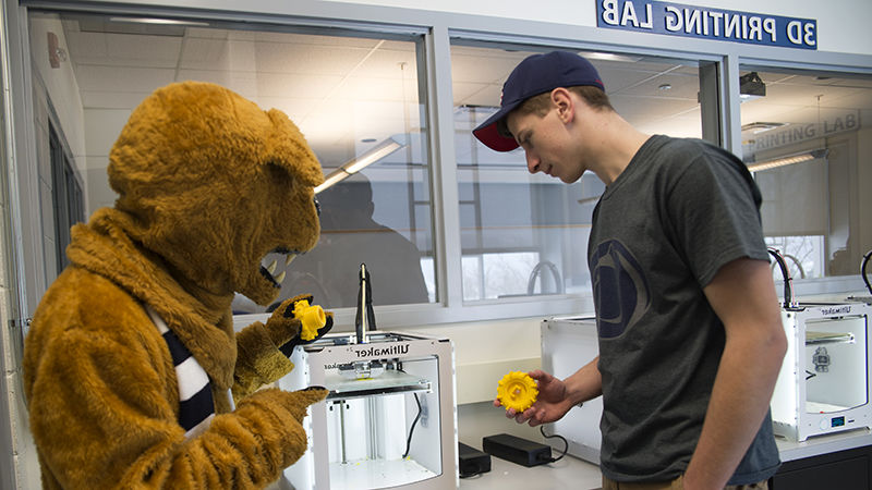 Student working in the 3D lab with the mascot.